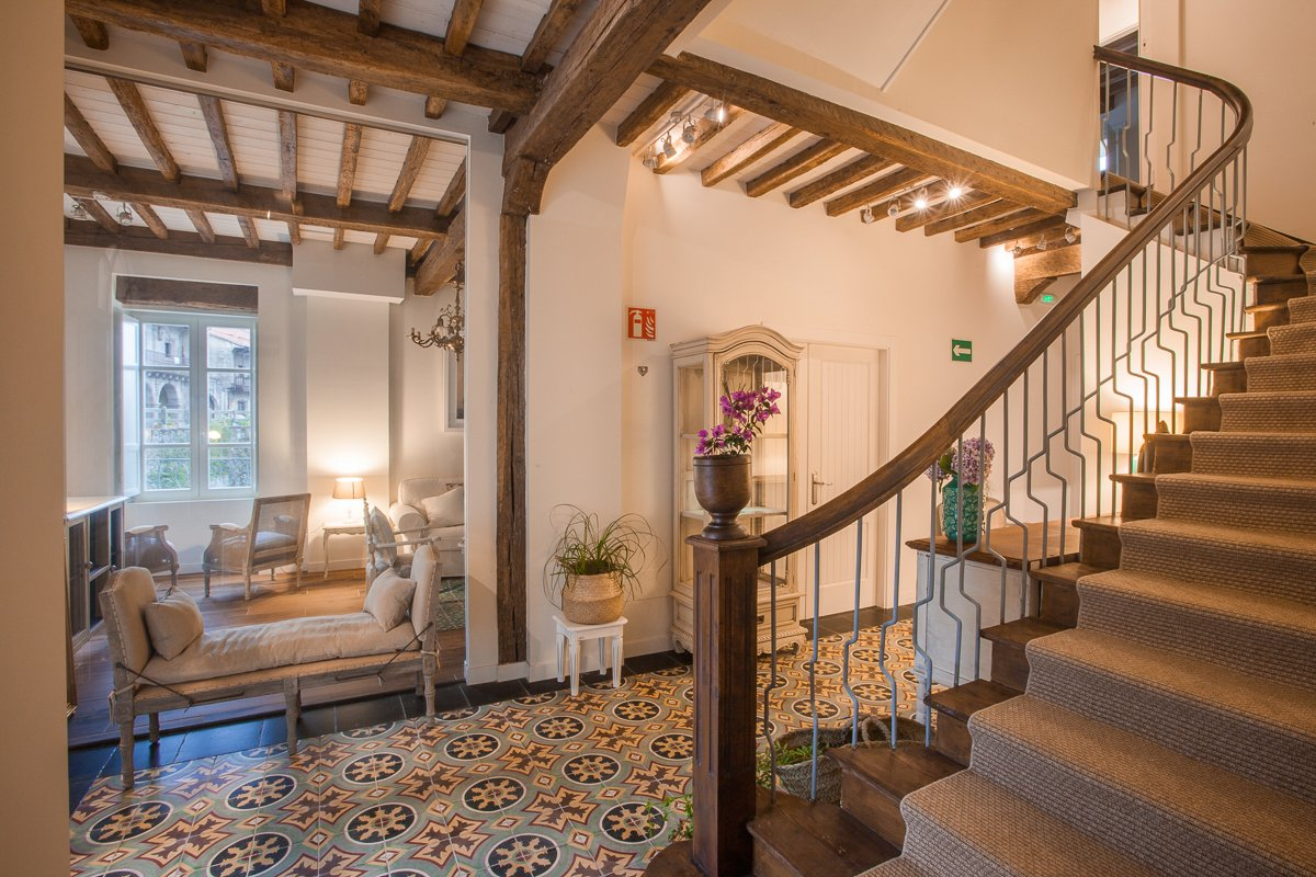 Hall de recepción con acceso la gran escalera de madera y vistas al salón