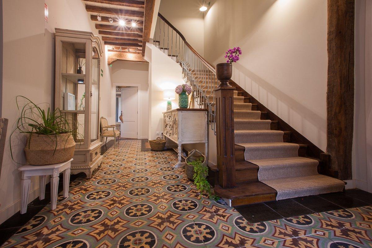 Hall de recepción de estilo rústico y gran escalera de madera original de la posada