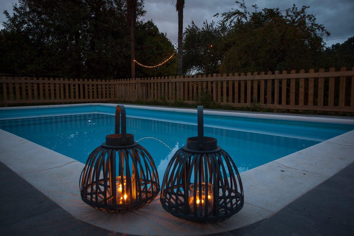 Piscina con velas por la noche en la Posada Seis Leguas