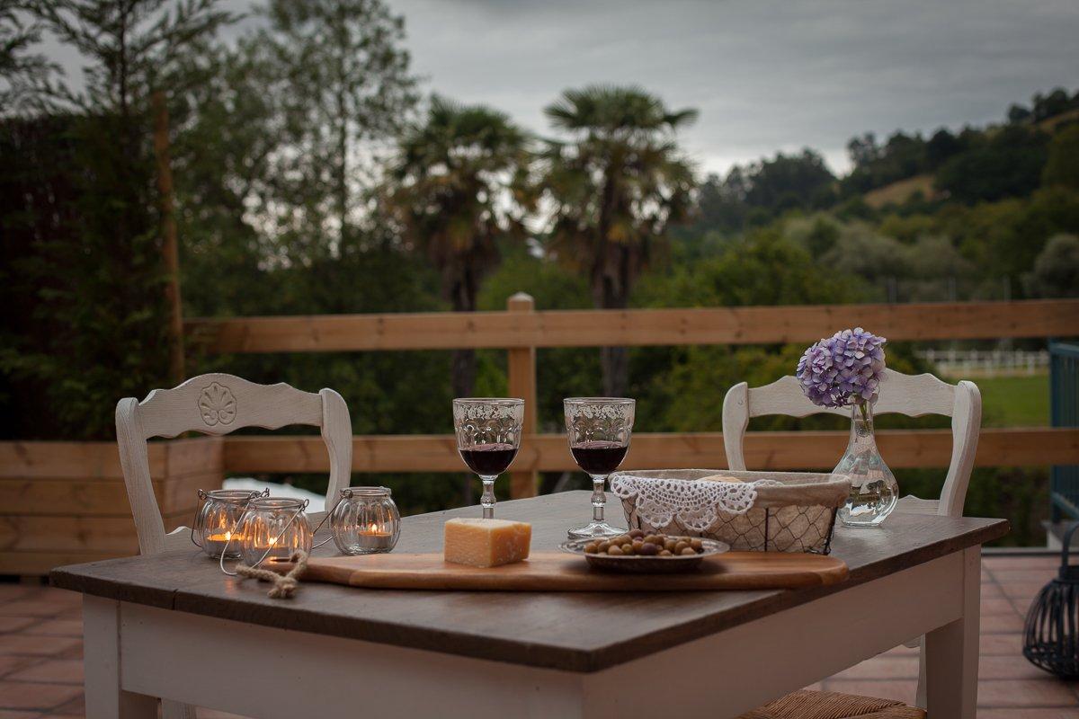 Vino y picoteo al atardecer en la terraza con vistas al jardín de la Posada